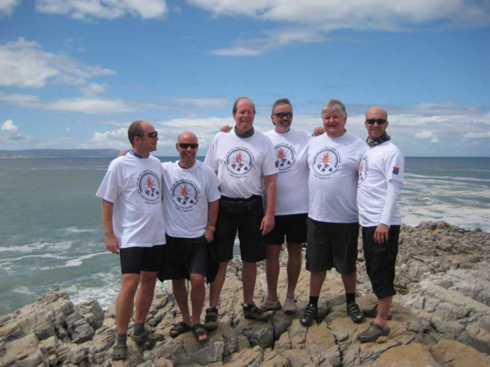 ABC bike and hike challenge - Gentlemen posing for a group photo by the ocean.